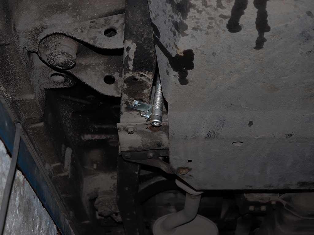 Заканчивается выхлопная труба около защиты двигателя.